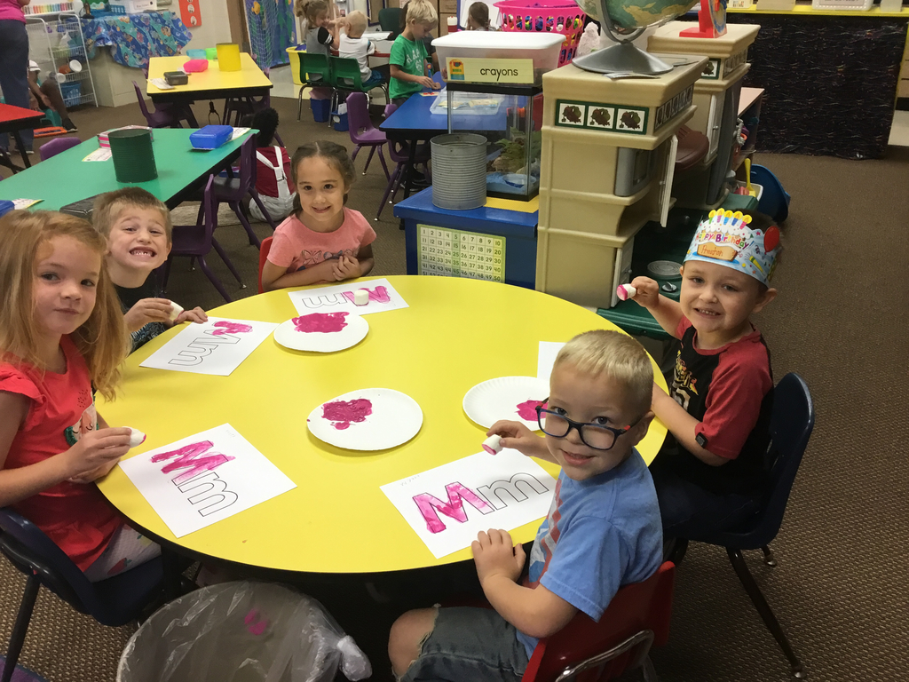 Painting the letter Mm using marshmallows and magenta paint!